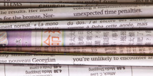 Detail of a pile of international newspapers. Great abstract newspaper background.