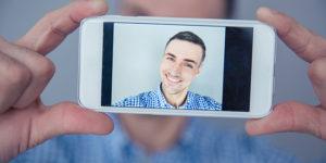 Cheerful man making selfie photo on smartphone